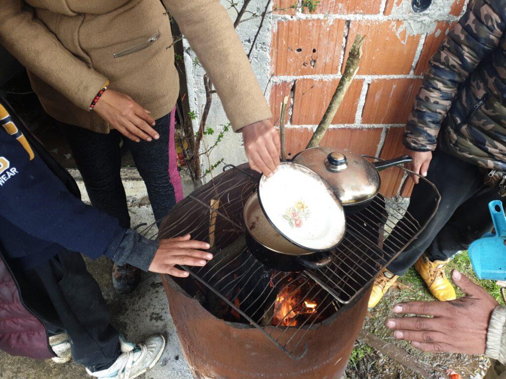 Schutzsuchende kochen Reis über einem Feuer in einem Squat in Bosnien