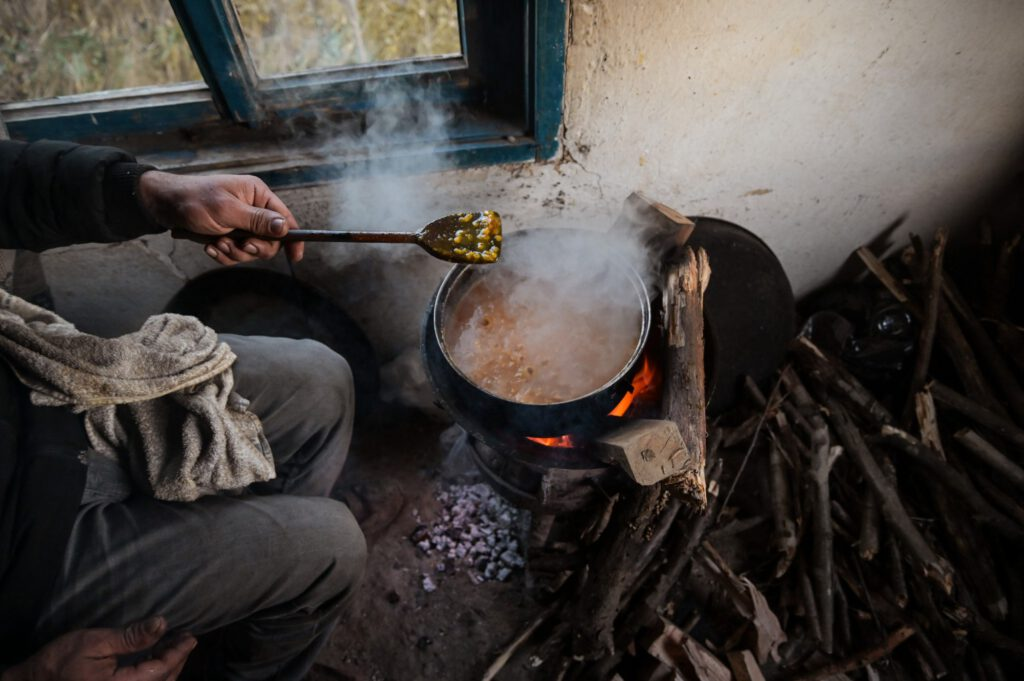 A refugee is cooking food over an open fire, only his hands are visible